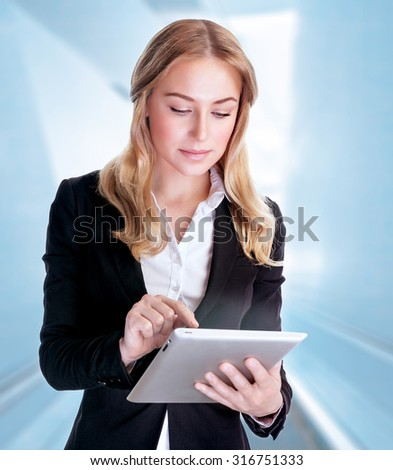 Portrait of beautiful serious business woman using touchpad, modern electronic technology, working in the office, conception of success - stock photo