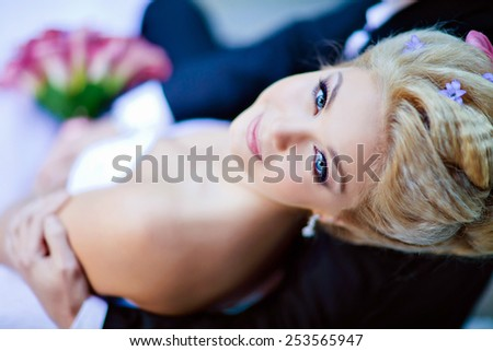 Portrait of beautiful sexy bride blonde in a white dress with purple Calla lilies in her hands, close up - stock photo