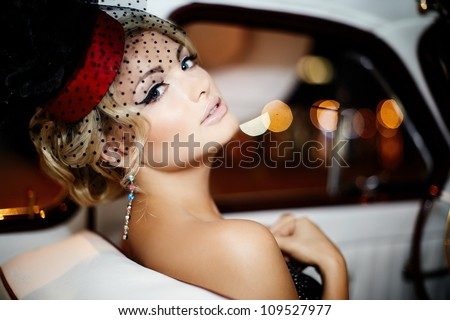 Portrait of beautiful sexy fashion girl model with bright makeup in retro style sitting in old car - stock photo