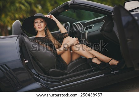 Portrait of beautiful sexy fashion woman model in summer hat and in black dress and luxury accessories with bright makeup sitting in luxury car. Young woman driving on road trip on sunny summer day. - stock photo