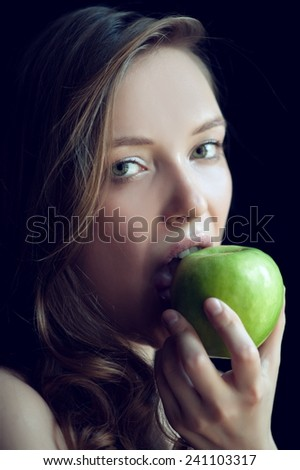 Portrait of beautiful sexy girl on a black background with apple - stock photo