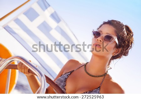Portrait of beautiful sexy woman behind wheel of luxury sailboat, serious captain driving water transport, enjoying active summer vacation  - stock photo