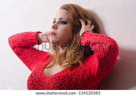 Portrait of beautiful sexy woman smoking a cigarette. - stock photo