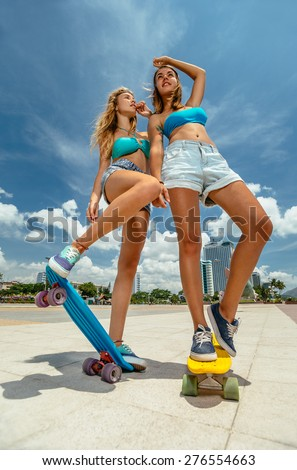 Portrait of beautiful skateboarding women on skateboards at summer park. - stock photo