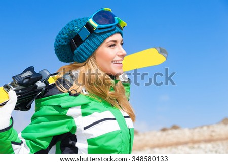 Portrait of beautiful skier woman over blue sky background, enjoying active winter sport, spending Christmas holidays in Alps, Europe - stock photo