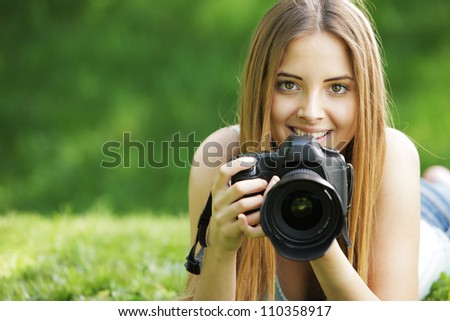 Portrait of beautiful smiling blonde girl , making photos at summer green park. - stock photo
