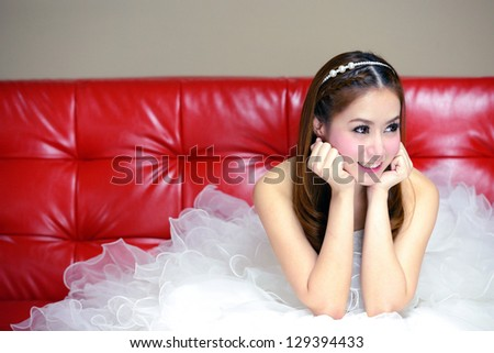 portrait of beautiful  smiling bride is on the red sofa - stock photo