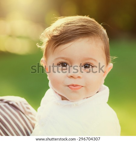 Portrait of beautiful smiling cute baby boy. 8 month old little child playing outside in green summer or spring park. - stock photo