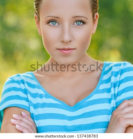Portrait of beautiful smiling dark-haired woman wearing striped blue t-shirt at summer green park. - stock photo