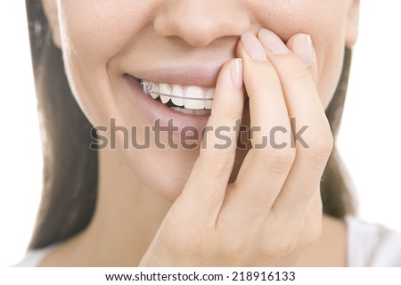Portrait of Beautiful smiling girl covering with hand her retainer for teeth, isolated on white background - stock photo