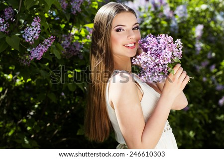 Portrait of beautiful smiling girl with a lilac flowers - stock photo