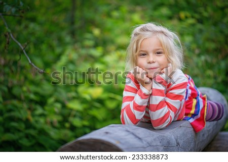 Portrait of beautiful smiling little girl lies on log in green city park. - stock photo