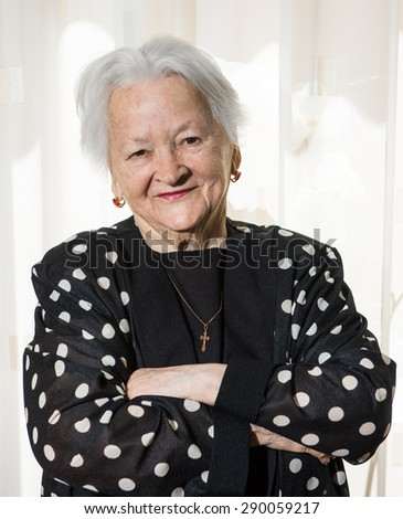 Portrait of beautiful smiling old woman at home - stock photo