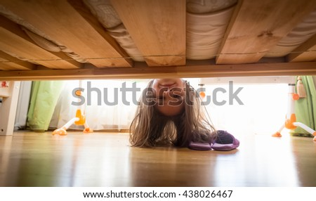 Portrait of beautiful smiling teenage girl looking under the bed for slippers - stock photo