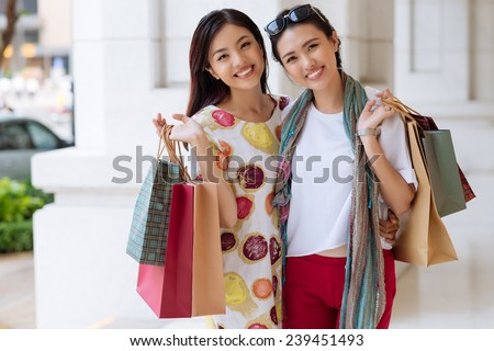 Portrait of beautiful smiling Vietnamese women holding shopping bags and looking at the camera - stock photo