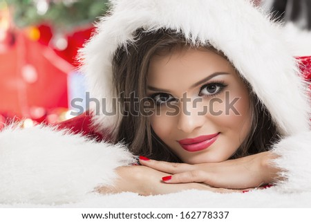 Portrait of beautiful smiling woman in Santa helper outfit with hood resting her chin on her hands while lying down. Studio shot. - stock photo