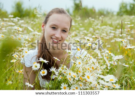 Portrait of beautiful smiling woman in the flower field - stock photo