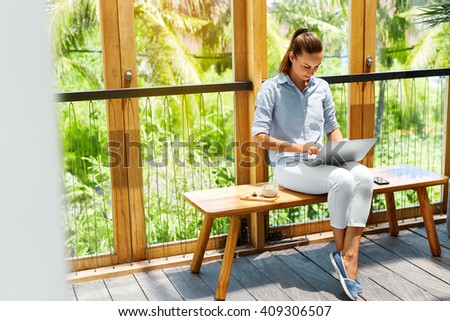 Portrait Of Beautiful Smiling Woman Typing On Notebook Keyboard While Working Online Using Laptop Computer. Female Sitting On Terrace Balcony At Cafe With Pc On Her Knees. Business People  - stock photo