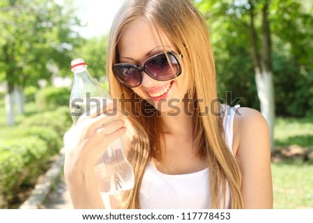 Portrait of beautiful smiling woman with bottle of water, outdoors - stock photo