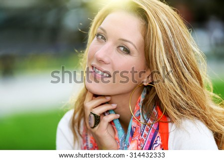 Portrait of beautiful smiling woman with colourful scarf - stock photo