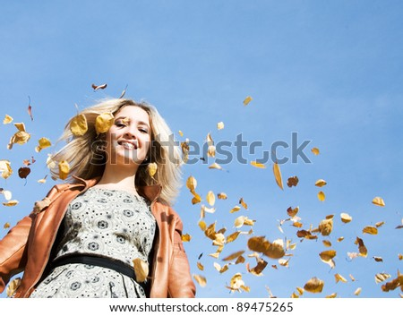 Portrait of beautiful smiling woman with falling autumnal leaves - stock photo