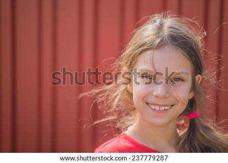 Portrait of beautiful smiling young girl on background of red metal fence. - stock photo