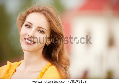 Portrait of beautiful smiling young woman close up on background of big house. - stock photo