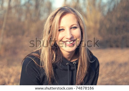Portrait of beautiful smiling young woman enjoying at the park - Outdoor. Warm colors - stock photo