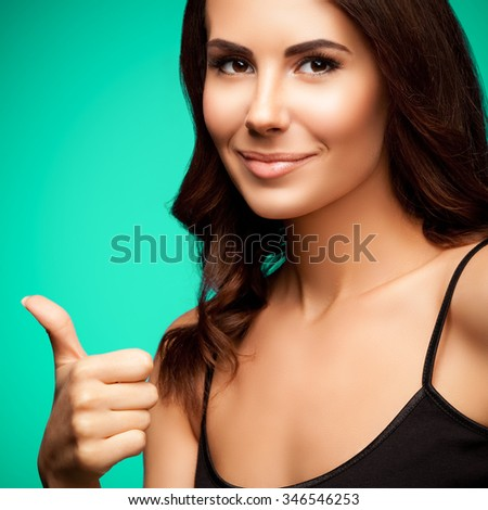 Portrait of beautiful smiling young woman in black tank top clothing, showing thumb up gesture, on green background - stock photo