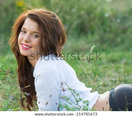 Portrait of beautiful smiling young woman in nature - stock photo