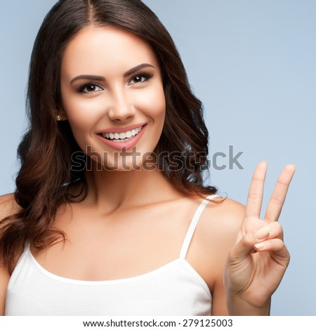 Portrait of beautiful smiling young woman showing two fingers or victory gesture, on grey - stock photo