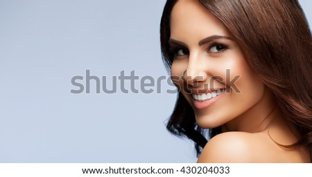 portrait of beautiful smiling young woman with naked shoulders, with copyspace, on grey background - stock photo