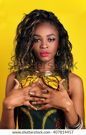 Portrait of beautiful South African young woman with curly loose hair and bright red lips wearing color dress over yellow background. Latin woman with makeup, nail polish and hairstyle. black woman. - stock photo
