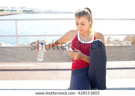 Portrait of beautiful sporty teenager girl sitting by sea outdoors, using smart phone technology to listen to music, holding mineral water, exercising. Adolescent sport lifestyle, outdoors exterior. - stock photo