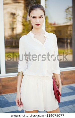 Portrait of beautiful stylish girl walking down the street - stock photo