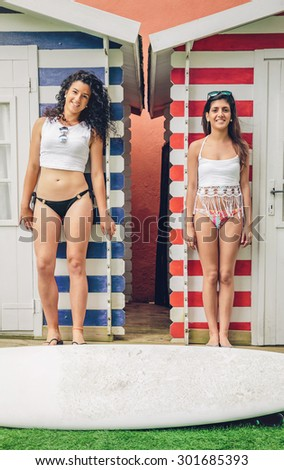 Portrait of beautiful surfer women couple with bikini and surfboard standing over a beach striped huts background. Summer leisure concept. - stock photo
