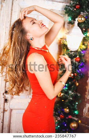 Portrait of beautiful sweet young woman in gorgeous evening dress over Christmas background. - stock photo