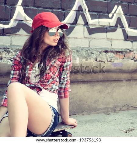 Portrait of beautiful teen girl sitting on skateboard over wall with abstract graffiti art. Urban outdoors, teenager's lifestyle. Toned. - stock photo