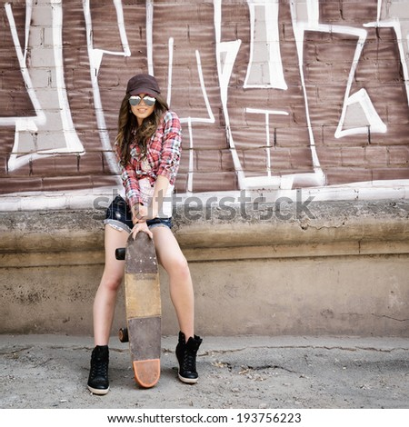 Portrait of beautiful teen girl standing on skateboard over wall with abstract graffiti art. Urban outdoors, teenager's lifestyle. Toned. - stock photo
