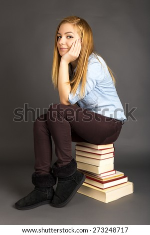 Portrait of beautiful teenage girl sitting on pile of books over gray background - stock photo