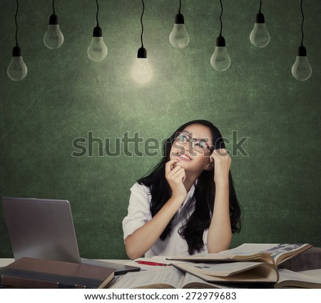 Portrait of beautiful teenage girl smiling happy under lamp while studying on the table - stock photo