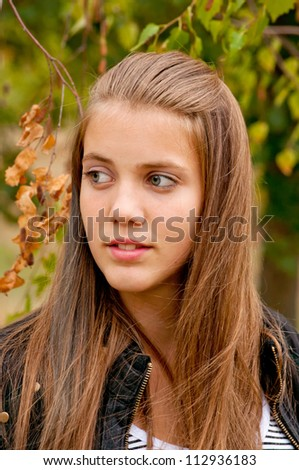 Portrait of beautiful teenage girl with yellow leaves in the background - stock photo
