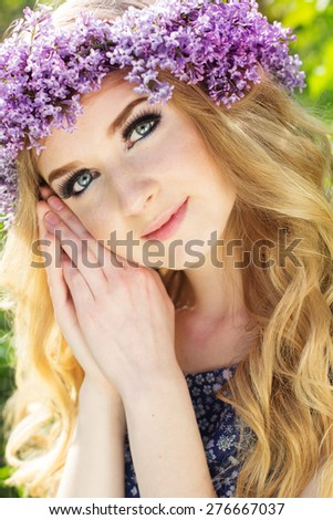 Portrait of beautiful teenager girl with wreath from purple lilac flowers - stock photo