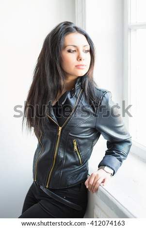 Portrait of beautiful thoughtful brunette posing near the window - stock photo