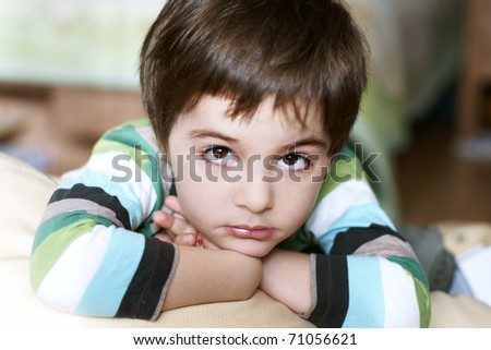 Portrait of beautiful thoughtful little boy with attentive look - stock photo