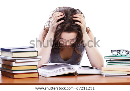portrait of beautiful tired brunette student girl sitting among the books - stock photo