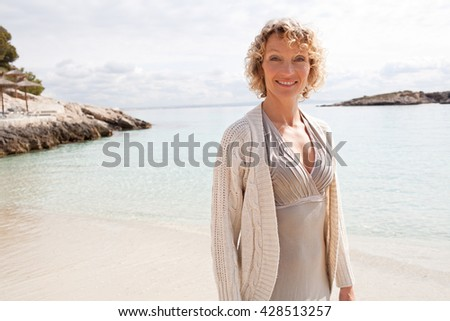 Portrait of beautiful tourist senior woman relaxing by the blue sea on holiday, smiling looking at camera on vacation, coastal outdoors. Healthy relaxing contemplating lifestyle, nature exterior. - stock photo