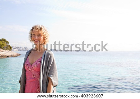 Portrait of beautiful tourist senior woman relaxing by the transparent blue sea on holiday, smiling on a sunny vacation, coastal outdoors. Healthy relaxing lifestyle, nature exterior. - stock photo