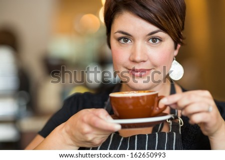 Portrait of beautiful waitress holding coffee cup in cafe - stock photo