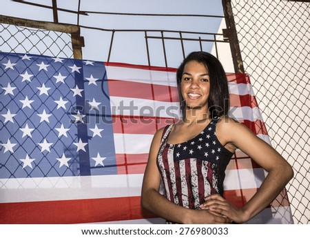 portrait of Beautiful woman, American flag on rusty metal fence. Patriotic concept. All American beauty.Cute young adult girl under  protection of  American flag hang outdoor against blue summer sky - stock photo